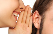 woman whispering in someone's ear